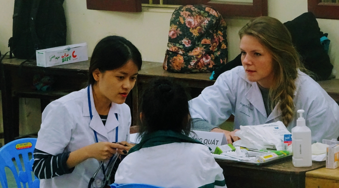 Two undergraduates in Vietnam working at an outreach during their internship for pre med students.